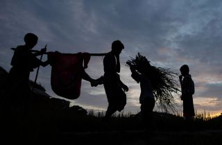 Rohingya refugees walk through a camp in Bangladesh after arriving from Myanmar.