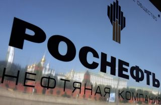 The walls surrounding the Kremlin are reflected on a plaque at the entrance of the oil company Rosneft's headquarters in Moscow.