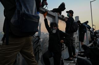 This photo shows pro-democracy protesters in Hong Kong fleeing from police by climbing over highway dividers during a mass rally on Dec. 1, 2019.