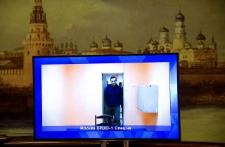 Opposition leader Alexei Navalny on Jan. 28, 2021, appears on a screen set up at a hall of the Moscow Regional Court.