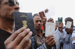 Foreign workers show their passports as they gather outside a Saudi immigration office in Riyadh, Saudi Arabia, on Nov. 4, 2013.