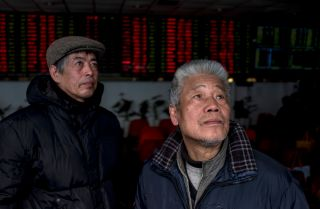 Investors monitor stock prices on computer screens at a brokerage house in Shanghai earlier this year.