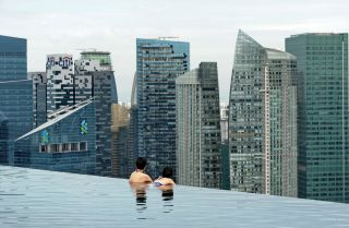 Tourists look at a view of the city skyline in Singapore.