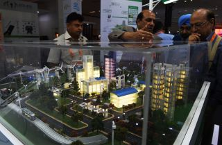 """Attendees at an expo in New Delhi, India, take in a model of a """"smart city,"""" an urban area wired with connected information and communication technology systems."""