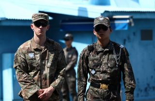 A U.S. soldier (left) stands guard next to a South Korean soldier (right) in Panmunjom, South Korea, on July 27, 2019, during a ceremony commemorating the 66th anniversary of the signing of the Korean War Armistice Agreement.