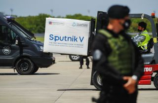 A member of the airport police stands guard as a forklift unloads a container full of Russia's Sputnik V COVID-19 vaccine from a plane in Ezeiza, Argentina, on Jan. 16, 2021.