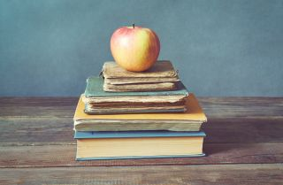 An apple sits atop a stack of books.