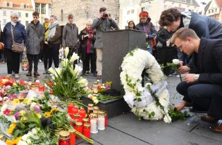 Mourners place flowers at a makeshift memorial on Oct. 10, 2019, at the market square in Halle, Germany, one day after a deadly anti-Semitic shooting.