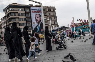 "Pedestrians cross Taksim Square in Istanbul, June 28. The poster behind them shows Turkish President Recep Tayyip Erdogan with a message that read: ""Thank you Istanbul."""