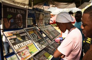 People read newspapers announcing the death of Tanzanian President John Magufuli in Dar es Salaam on March 18, 2021.
