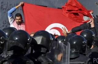 Police block protesters from accessing the parliament building on Jan. 26, 2021, in Tunis, Tunisia.