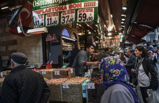 """Vendors sell nuts as people shop under a banner reading """"An End to Inflation"""" in Istanbul's Eminonu neighborhood on Nov. 6, 2018."""