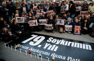 People hold pictures depicting victims of the Dersim operation in the 1930s, behind a placard marking the 79th anniversary of the genocide during a demonstration on May 4, 2016 in Istanbul.