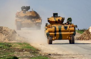 A Turkish military infantry fighting vehicle (IFV), followed by a battle tank, is seen along the M4 highway in northern Syria on March 15, 2020.