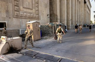 U.S. soldiers (L) on May 30, 2021, next to the former Baath Party headquarters near the entrance to the Green Zone in Baghdad.