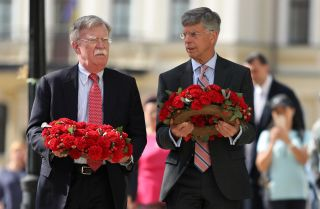 U.S. national security adviser John Bolton (L) and U.S. Ambassador to Ukraine William Taylor prepare to lay flowers commemorating Ukrainian soldiers who died in eastern Ukraine during a visit to Kyiv on Aug. 27, 2019.