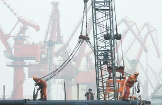 Chinese workers prepare to load pipes onto a ship in the port of Lianyungang on Jan. 14, 2019.