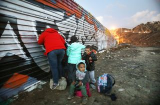 A picture showing Honduran migrants gathering on the Mexican side of the U.S.-Mexico border fence near Tijuana after unsuccessfully attempting to cross into the United States, Dec 1.