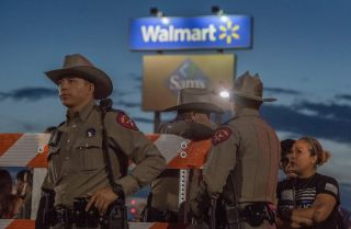 Texas State Troopers keep watch at the makeshift memorial for victims of the shooting that left a total of 22 people dead at the Cielo Vista Mall WalMart in El Paso, Texas, on August 6, 2019.