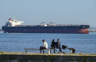 People relax on the bank of the Tagus River where Venezuelan PDVSA oil tanker Rio Arauca lies at anchor, having been impounded by Portuguese authorities for nearly two years due to unpaid debt, March 9.
