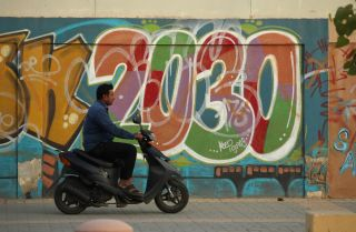 A man rides past graffiti alluding to Vision 2030