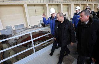 Vladimir Putin walks alongside workers at a hydroelectric plant.