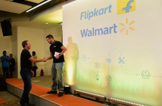 The CEOS of Walmart and Flipkart shake hands at an event in India.
