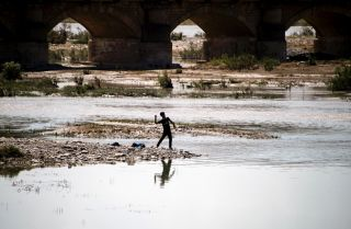A boy throws a stone into a river near Arbil, the capital of Iraqi Kurdistan.