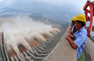Workers watch in 2012 as water is released from the Three Gorges Dam, a gigantic hydropower project on the Yangtze River in central China.