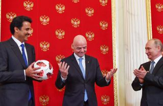 Qatari Emir Sheikh Tamim bin Hamad al-Thani (L) smiles at FIFA President Gianni Infantino (C) and Russian President Vladimir Putin at the end of the 2018 World Cup in Russia. As part of the closing ceremony, Putin passed a soccer ball to al-Thani, whose country will hold the next tournament in 2022, in a symbolic gesture.