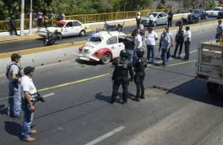 Authorities work at the scene where four racketeering suspects where shot down by security forces during a shoot-out along a highway in Acapulco in Guerrero on March 30, 2019.