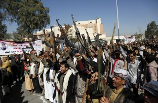 Houthi supporters hold up firearms as they protest the U.S. decision to designate the Houthi movement as a terrorist organization outside the closed American embassy on Jan. 18, 2021, in Sana'a, Yemen.