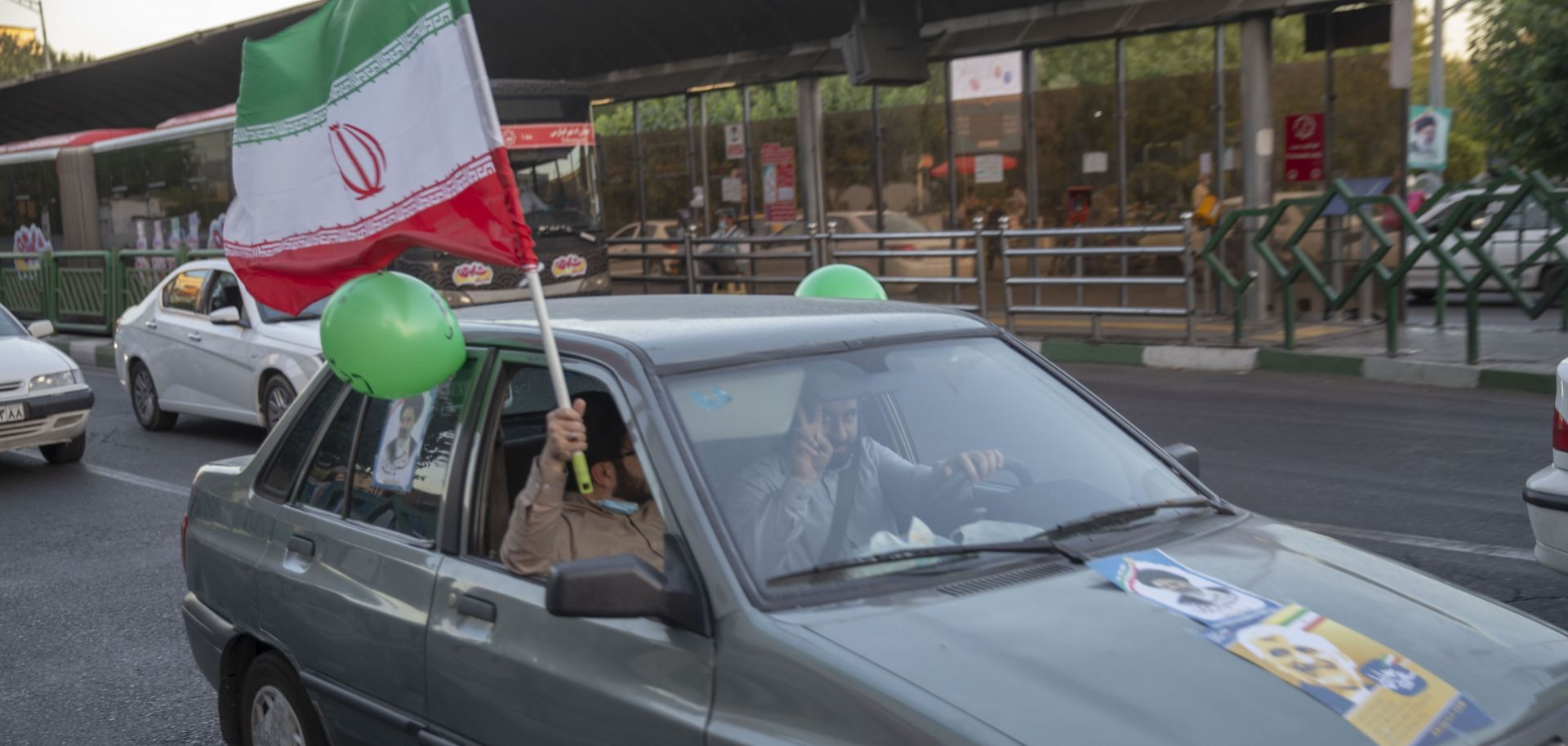 Supporters of Iranian presidential candidate Ebrahim Raisi hold an Iranian flag out of a car window on a street in Tehran on June 11, 2021.