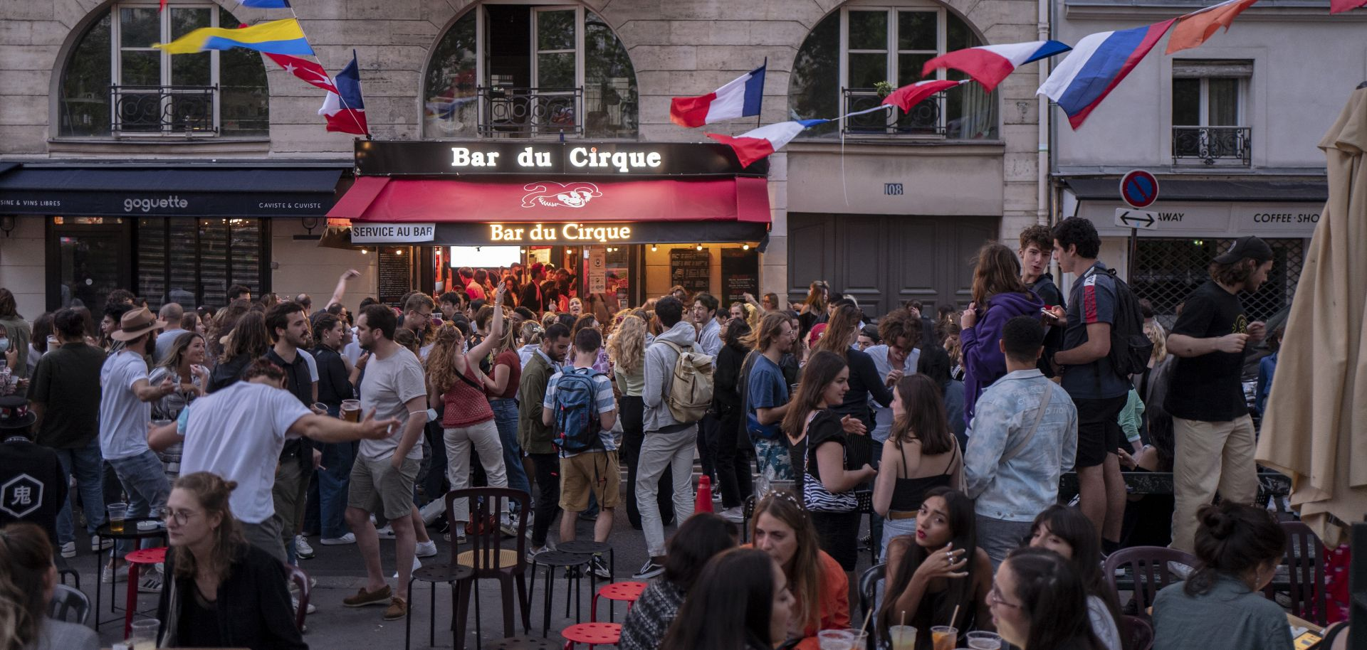 People dance in front of a bar in Paris on June 21, 2021, after the French government lifted the national curfew.
