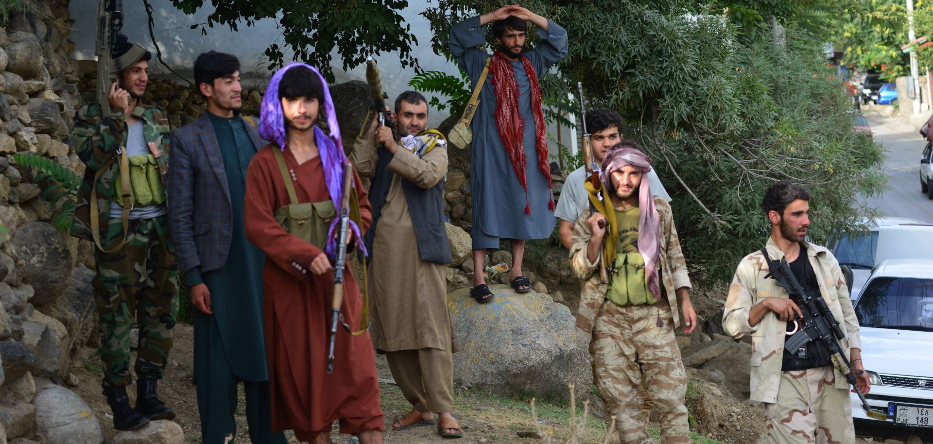 Armed men supporting Afghan security forces against the Taliban stand along a road in Panjshir on Aug. 18, 2021.