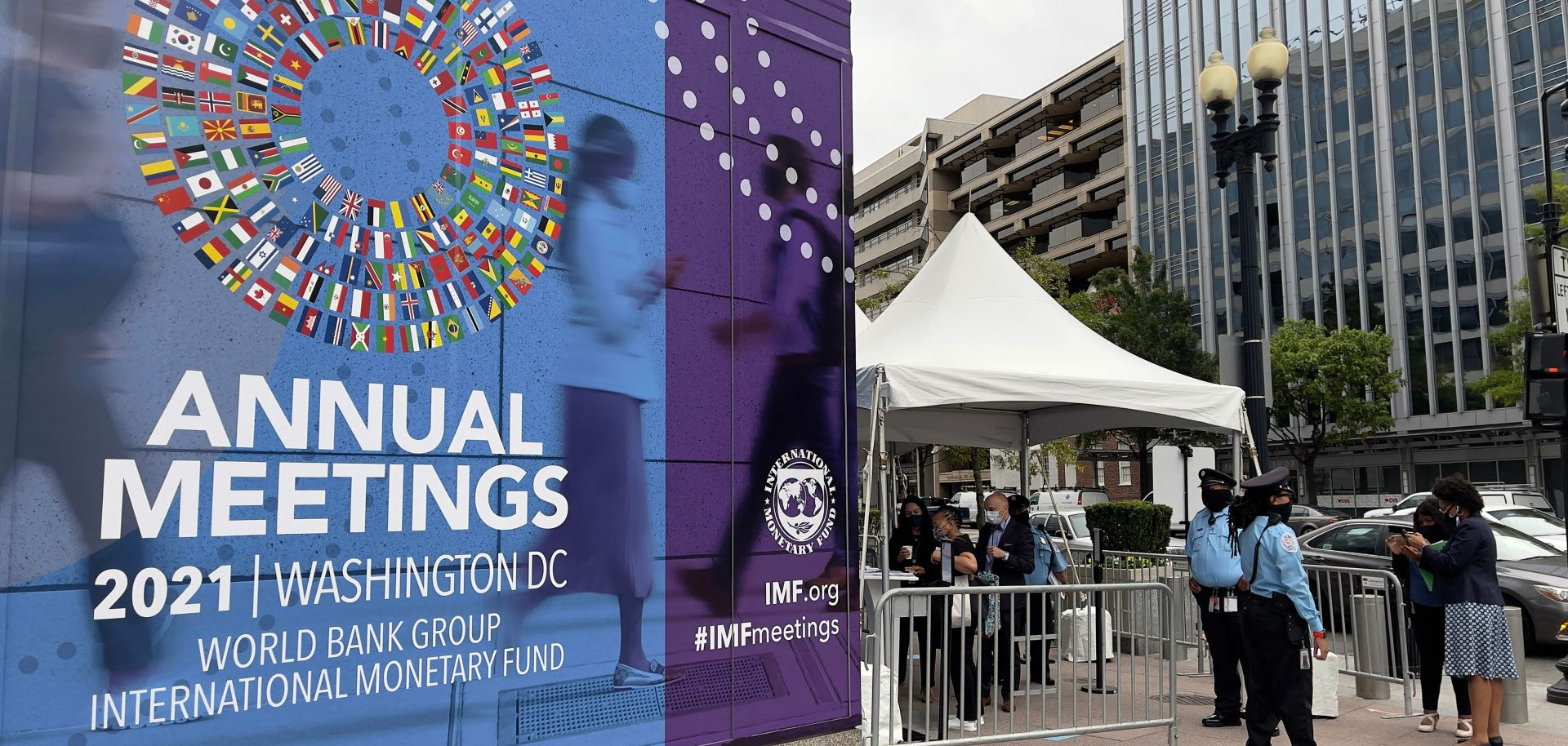People wait outside the entrance to the annual meetings of the World Bank and International Monetary Fund (IMF) outside the IMF headquarters in Washington D.C. on Oct. 11, 2021.