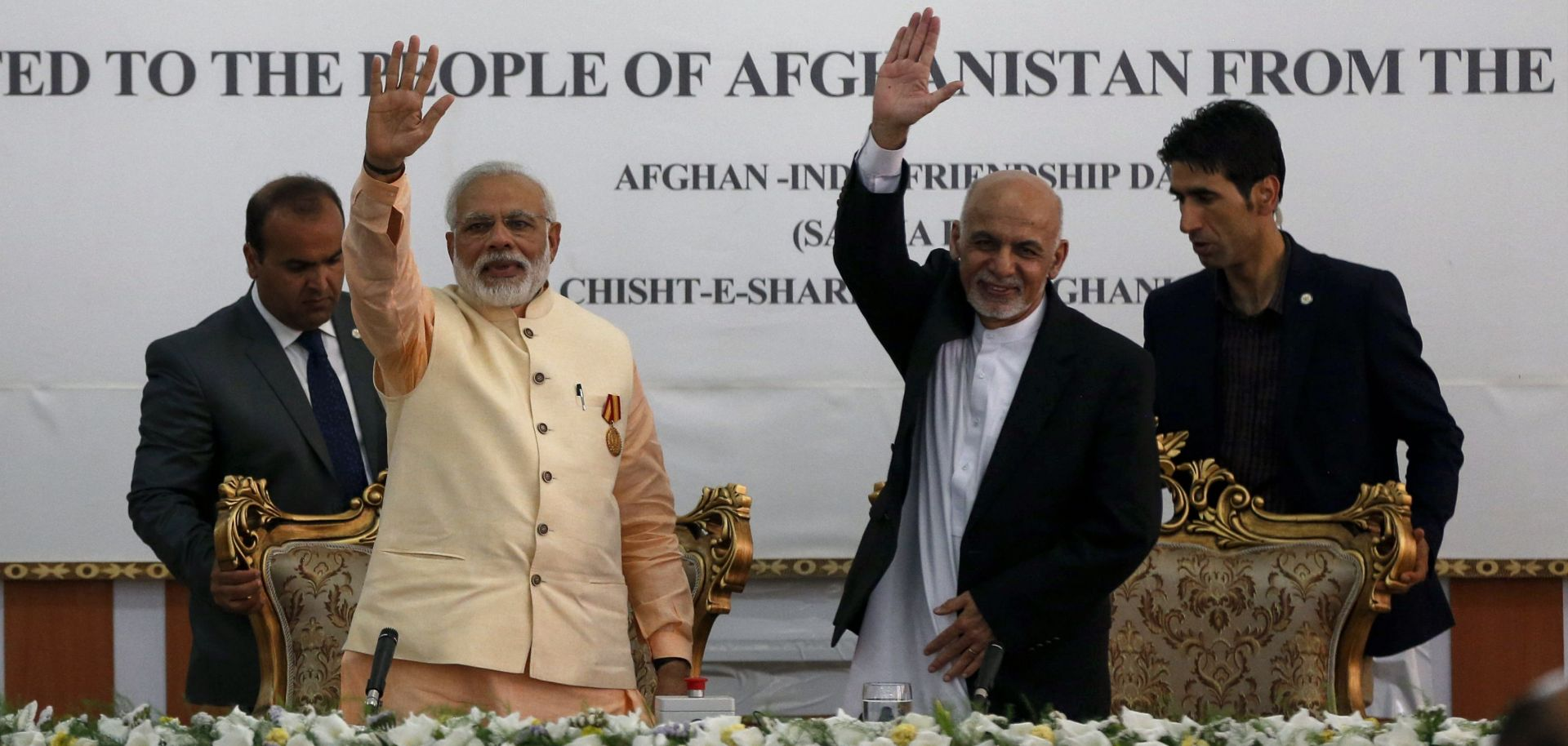 Indian Prime Minister Narendra Modi (left) and then-Afghan President Ashraf Ghani wave during the inauguration of the Afghan-India Friendship Dam in Herat, Afghanistan, on June 4, 2016.