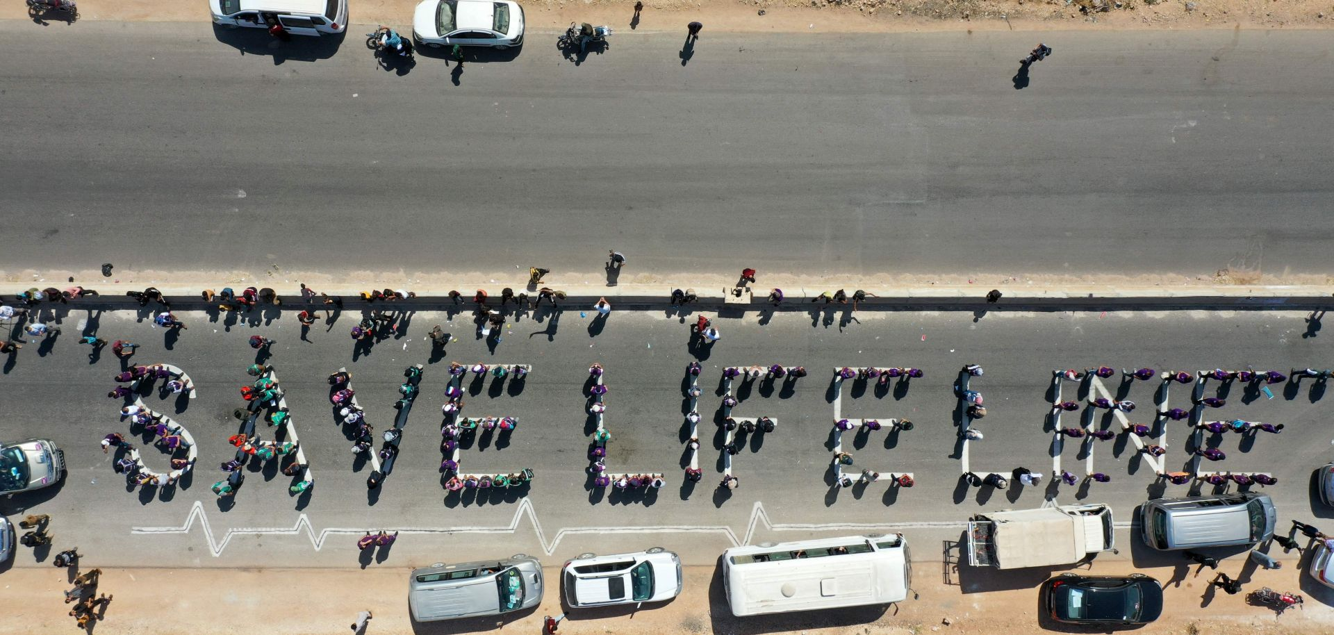Civilians and humanitarian workers form a human chain calling for the continuation of U.N.-authorized aid near Syria's Bab al-Hawa border crossing with Turkey.