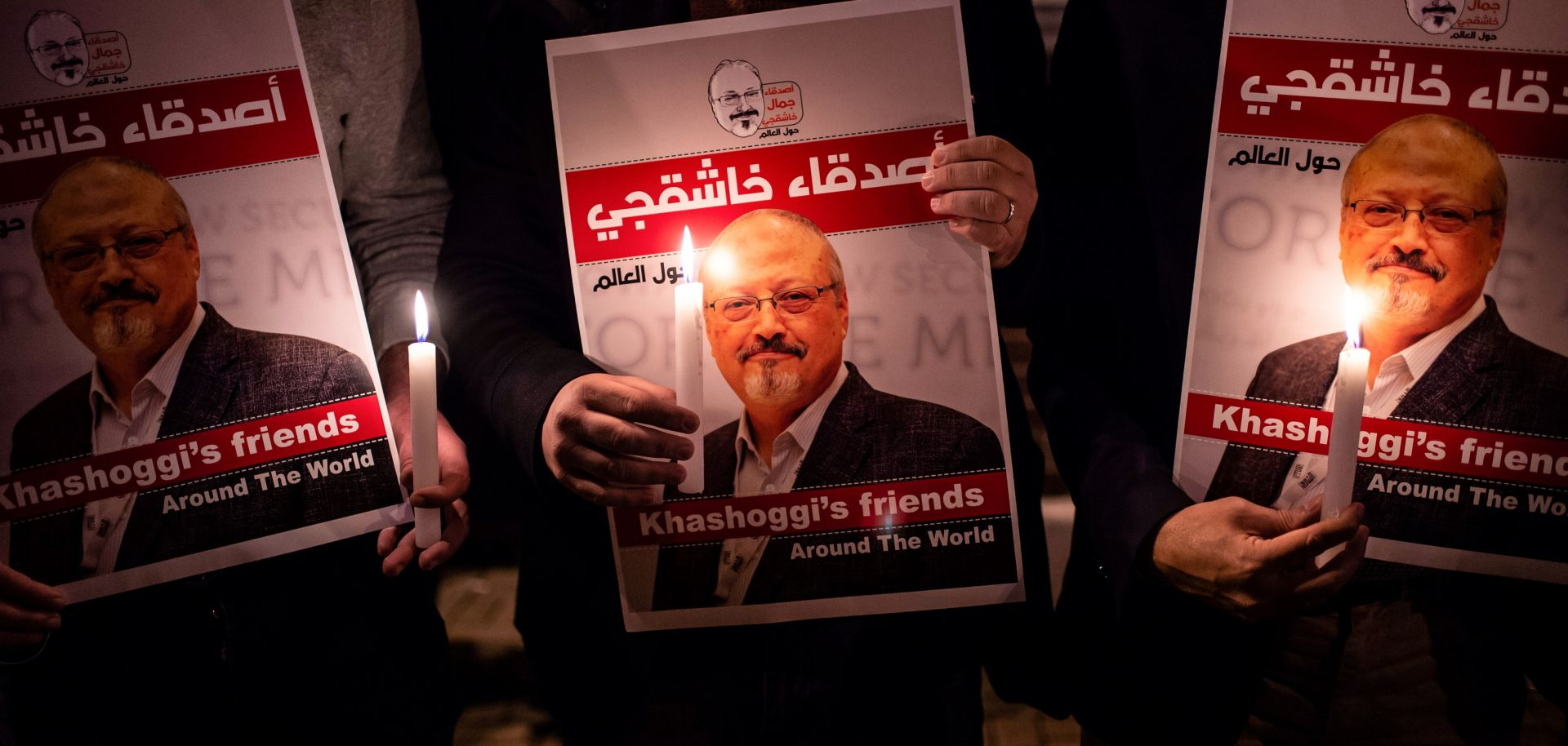 People hold posters depicting murdered Saudi journalist Jamal Khashoggi during a candlelit vigil outside the Saudi consulate in Istanbul on Oct. 25, 2018.
