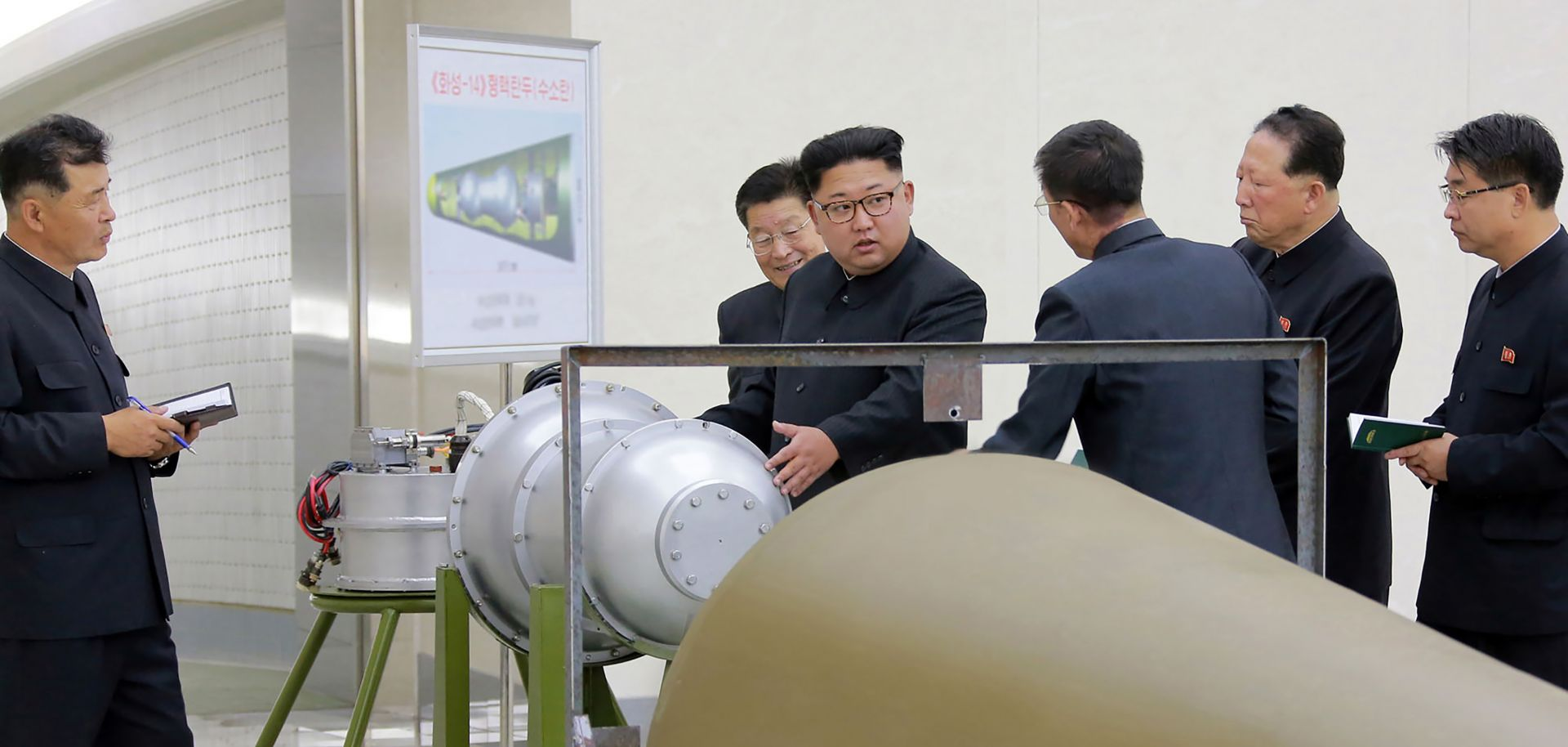 An undated picture released by North Korea's official Korean Central News Agency on Sept. 3 shows North Korean leader Kim Jong-Un (C) looking at a metal casing with two bulges at an undisclosed location.