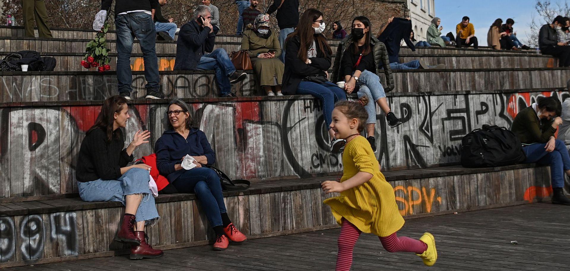 A child runs past people sitting near the Galata Bridge in Istanbul, Turkey, on Feb. 8, 2021.