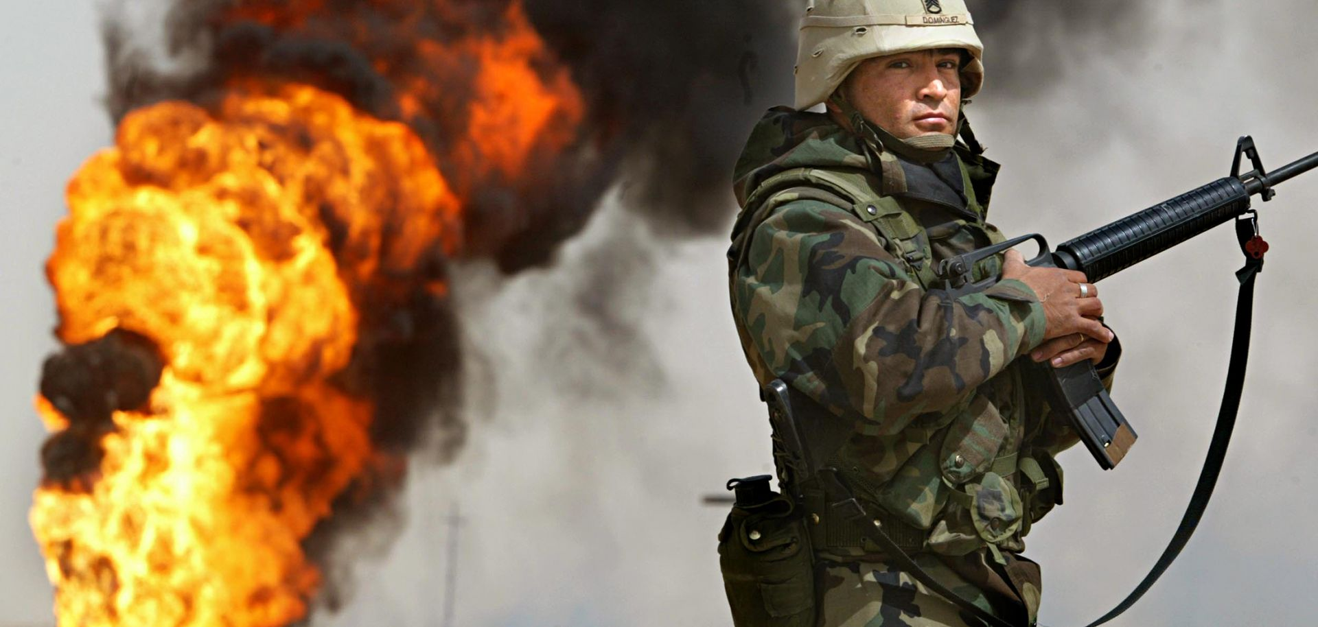 U.S. Army Staff Sgt. Robert Dominguez stands guard next to a burning oil well in the oil fields of Rumaila, Iraq, on March 27, 2003.