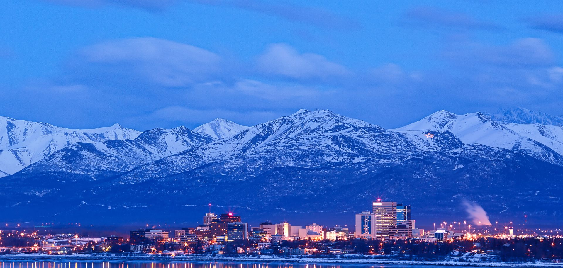 A skyline view of Anchorage, Alaska, and the Chugach Mountains at dusk.