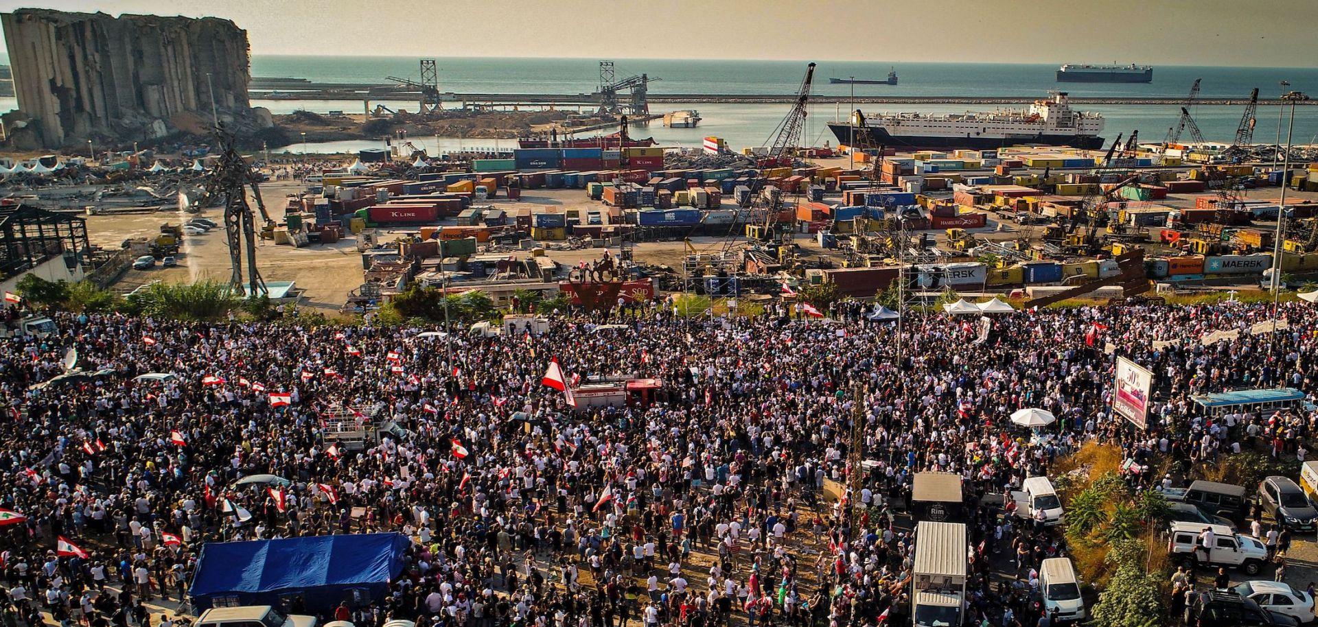 An aerial photo taken on Aug. 4, 2021, shows demonstrators gathered outside the port in Beirut, Lebanon, one year after the explosion ravaged the capital city.