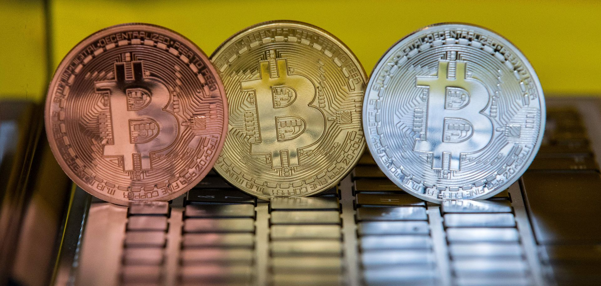 Physical representations of Bitcoin tokens, a digital currency, stand on a computer at a shop in Tel Aviv, Israel.