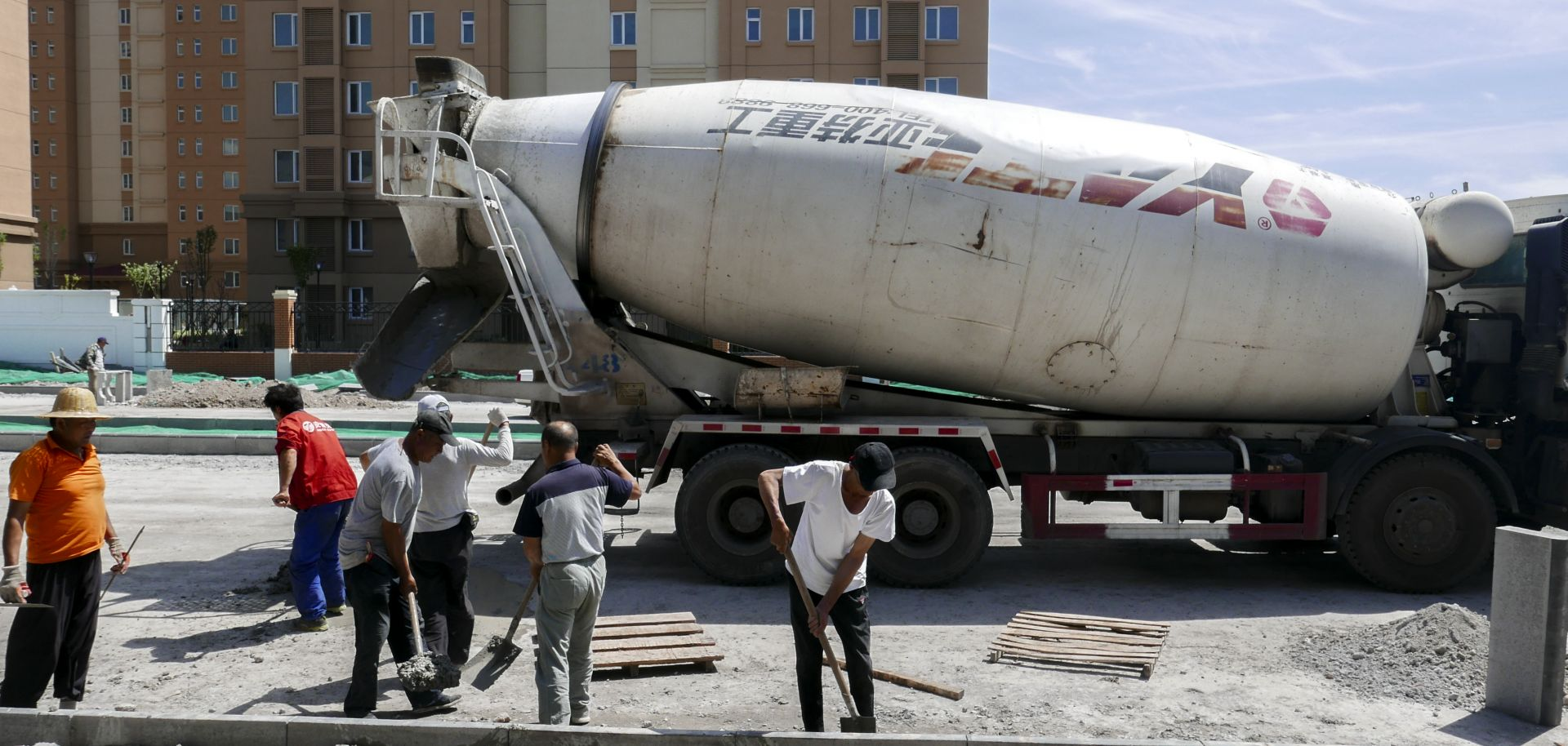 A cement tank car and workers are working on a construction site of a new residential district.