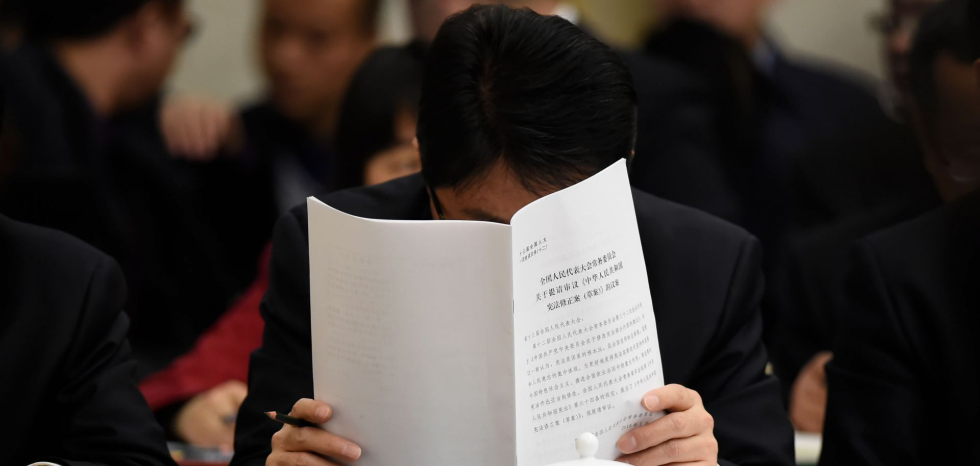 A delegate catches up on some reading during a meeting of the Gansu delegation at the National People's Congress in March 2018.