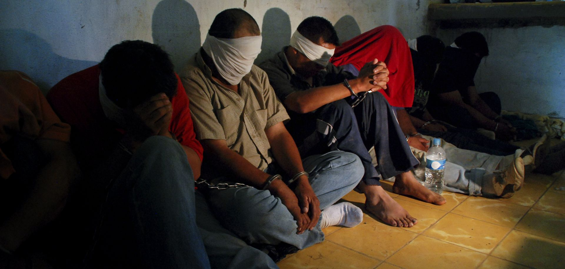 A group of people kidnapped by alleged drug-traffickers, sit on the floor after being rescued.