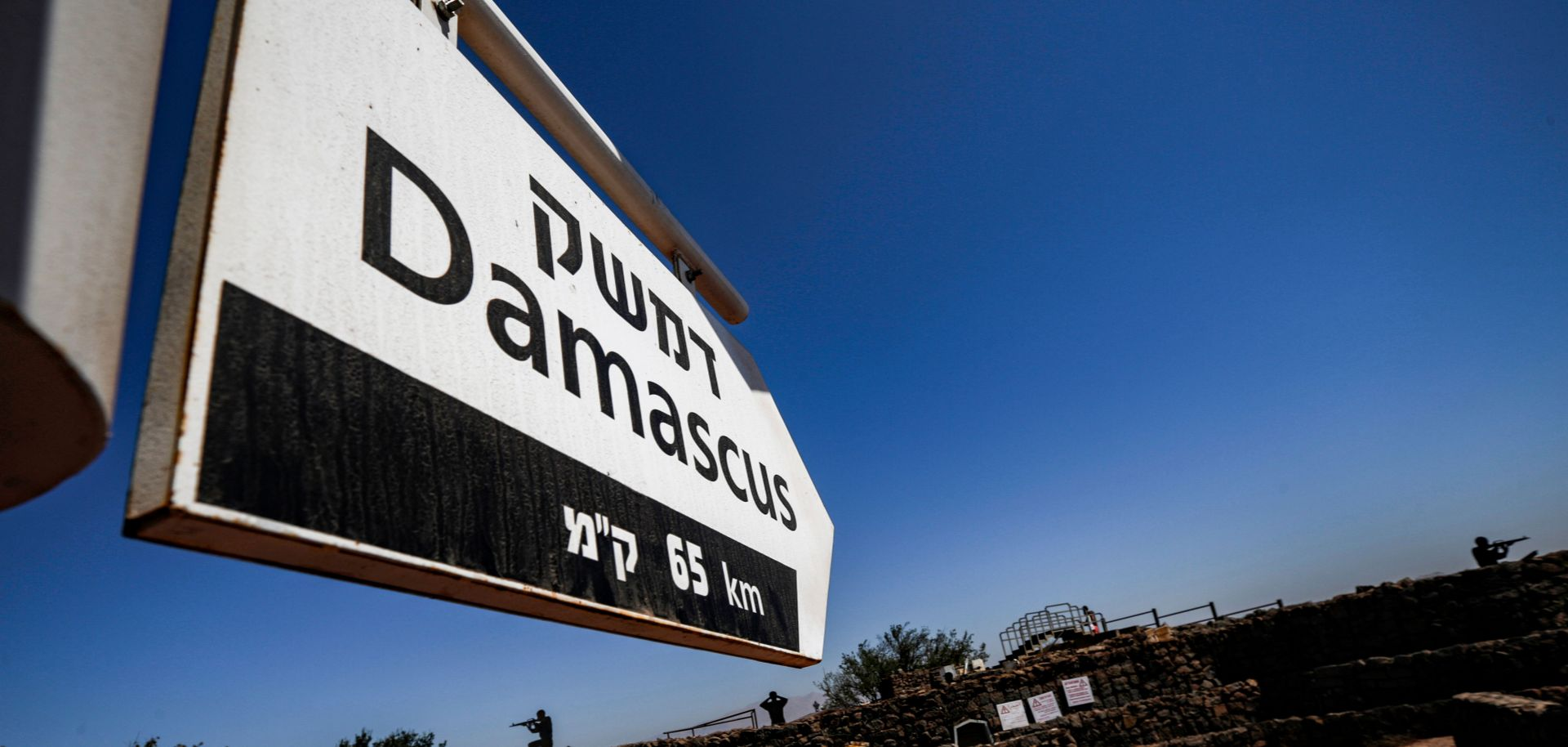 This picture taken on Aug. 25, 2019, from a tourist lookout point at an Israeli army outpost on Mount Bental in the Israeli-annexed Golan Heights shows a directional sign for Damascus.