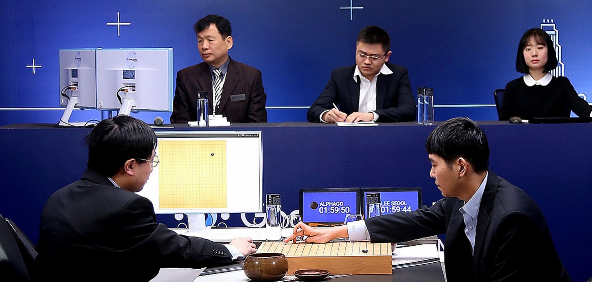South Korean professional Go player Lee Sedol (R) puts his first stone in a match against Google artificial intelligence program AlphaGo, which eventually won four of five games.